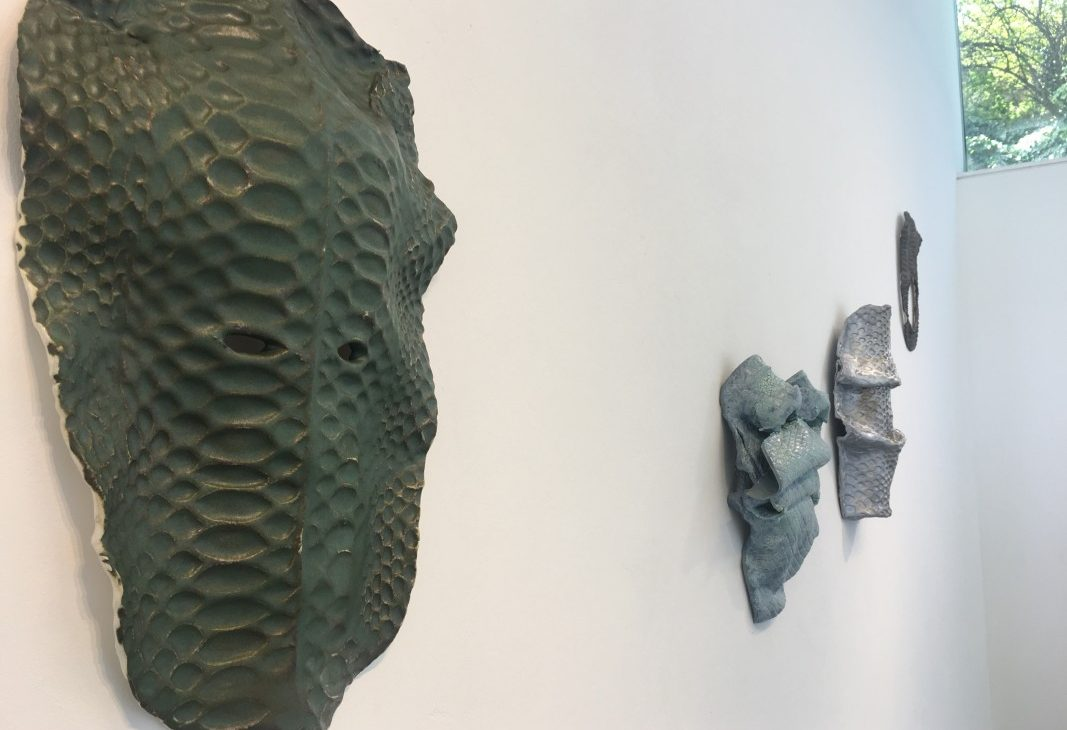 Four glazed ceramic wall pieces are in a row at varying heights, they each look like different masks and have repeat patterns like scales