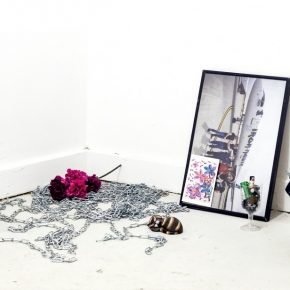 View of a corner with objects on the floor, components inclue: a silver chain, pink and purple flowers, wine glass with batteries, plastic cat, a framed picture and postcard leaning against the wall, a glass lantern with a bag draped on it