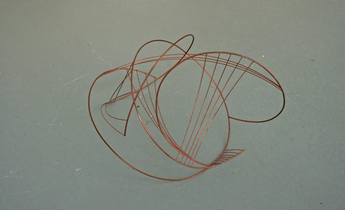 An abstract copper wire sculpture constructed from loops and lines is displayed on the floor