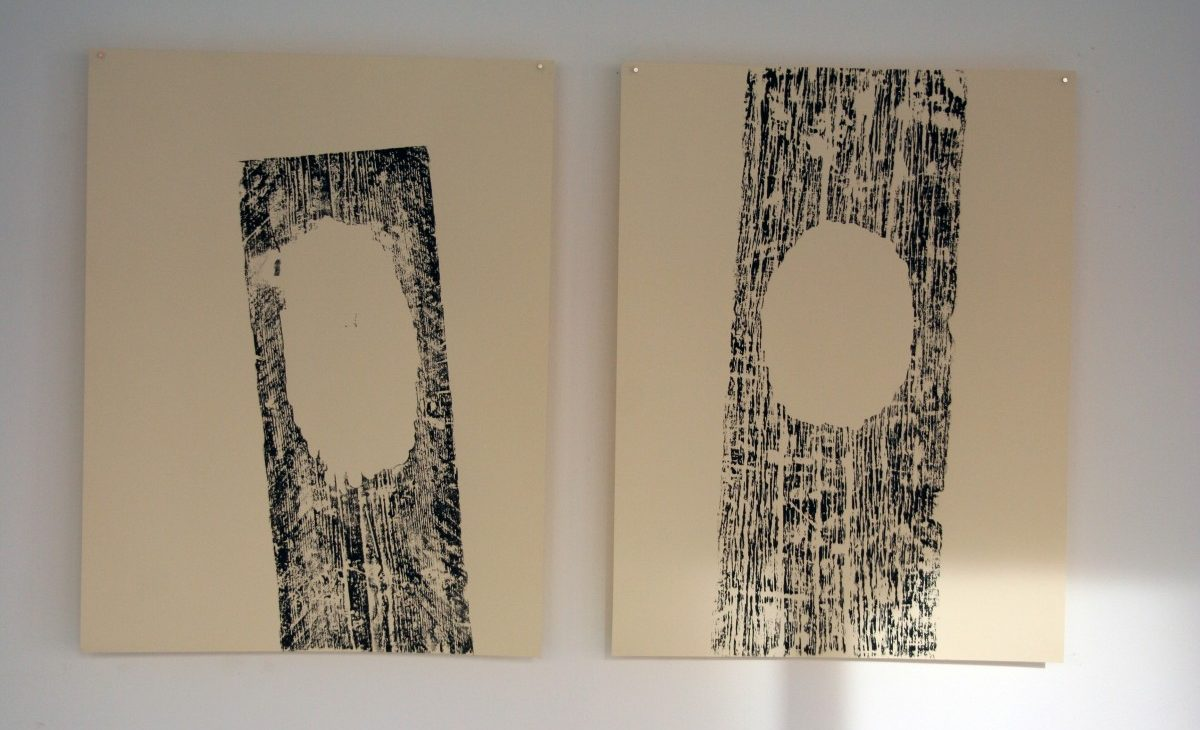 Two woodblock prints in black ink on cream paper; Woodgrain stripes with an oval hole showing cream paper
