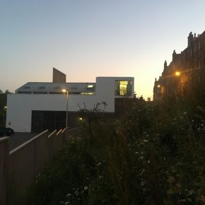 Street level view of the Edinburgh Sculpture Workshop building; Apartment lights are on; sun is setting