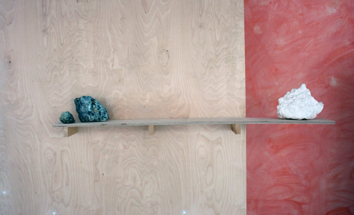Detail of a birch plywood shelf on a freestanding plywood sheet with a plaster cast rock counterweighted by two rocks. The plaster cast is white against a washed out terracotta coloured wall