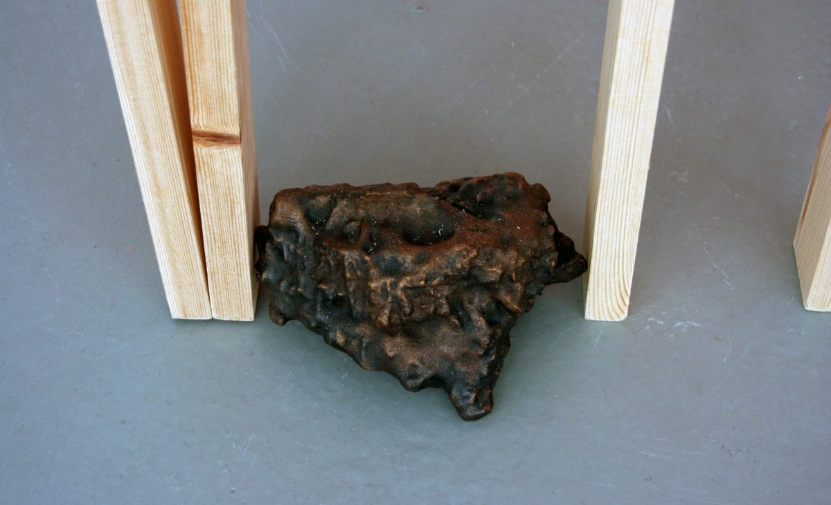 Close up of a bronze casted rock between wooden lengths, displayed on the floor