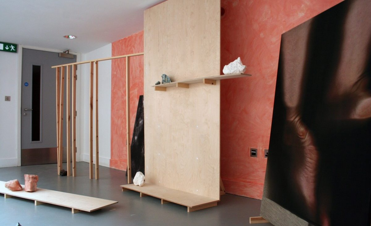 Installation view of salt, plaster cast and bronze cast rocks displayed on birch plywood and wooden length supports. With stretched images on fabric of scanned feet, rocks and moss against a washed out terracotta coloured wall