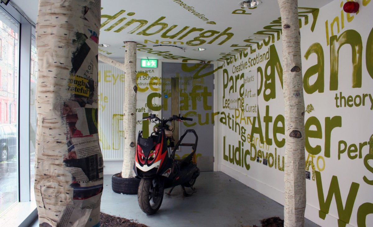 Detail view of three paper mache silver birch tree trunks sitting in dirt and bark, with a red, white and black motorcycle in the background, surrounded by alternate sizes of text painted in green on the white walls and ceiling and the grey door, excerpts include: Edinburgh, neomedievalism, Ludic, Creative Scotland, craft, creative, curating, learning