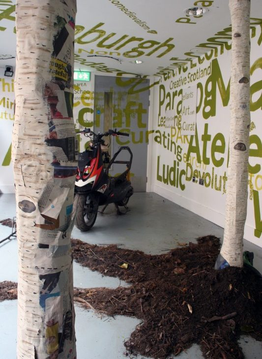 Detail view of two paper mache silver birch tree trunks sitting in dirt and bark, with a red, white and black motorcycle in the background, surrounded by alternate sizes of text painted in green on the white walls and ceiling and the grey door, excerpts include: Edinburgh, neomedievalism, Ludic, Creative Scotland, craft, creative, curating, learning