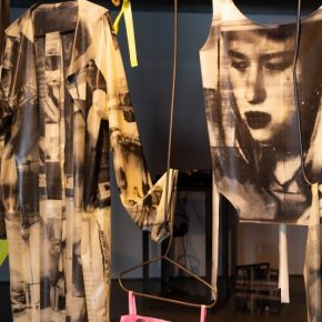 Blacksmith forged coat hangers and hooks hang from the ceiling holding white and pink latex garments, each with collaged black and white images of zoomed in faces and profiles