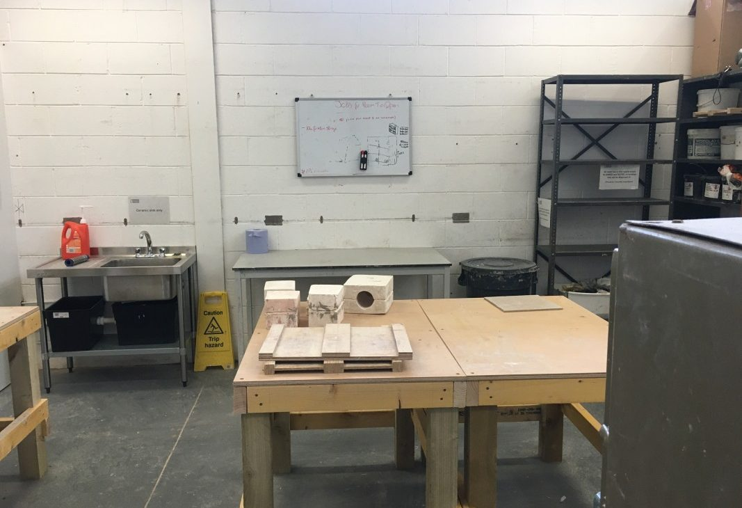 Two work tables sit together in the centre of a workshop with plaster slip cast moulds sitting on top of them