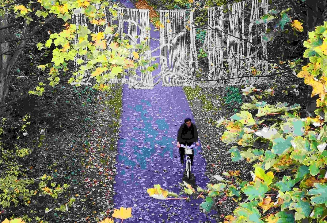 View onto cycle path with a cyclist moving underneath a macrame artwork made from ropes and knots installed at height between two trees