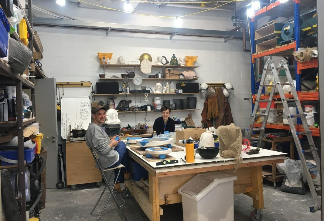 Two artists in conversation, sit at a large white work table, making plaster jackets for mould making