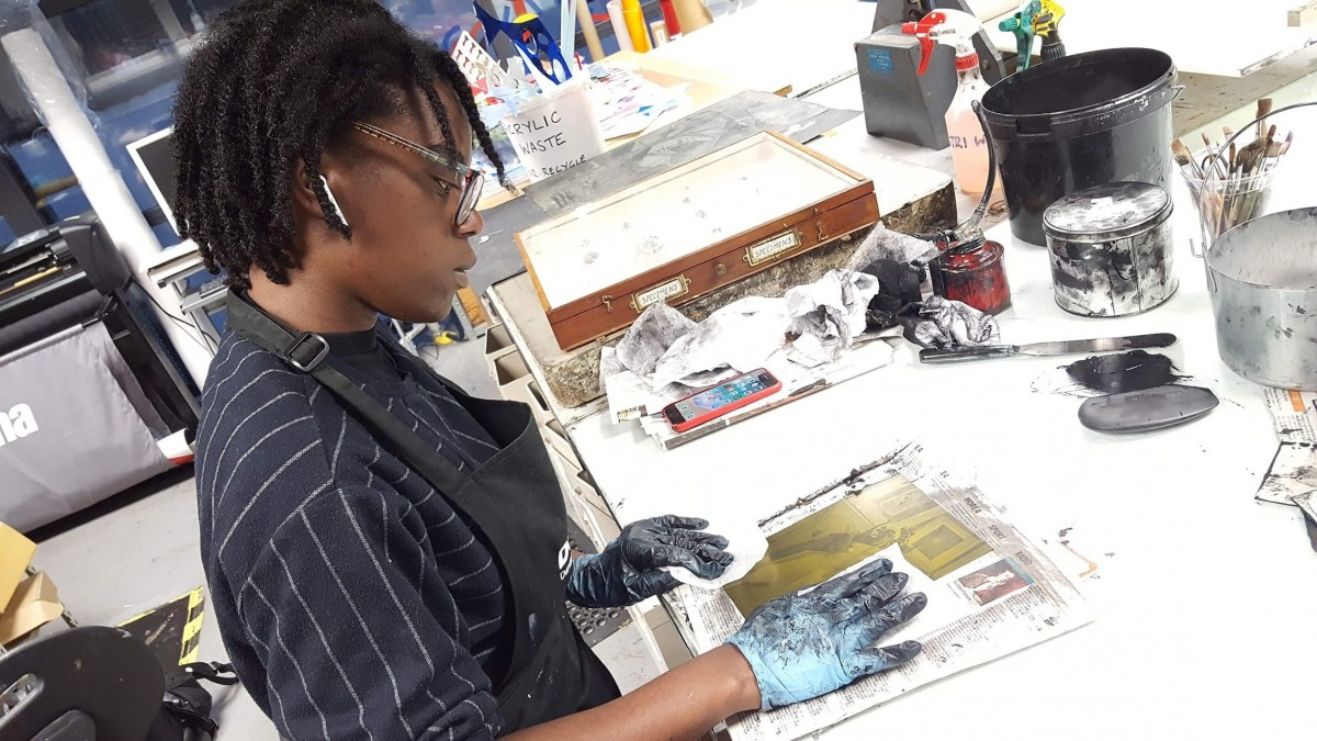 Artist Sekai Machache standing in front of a large print table wiping back an etching plate