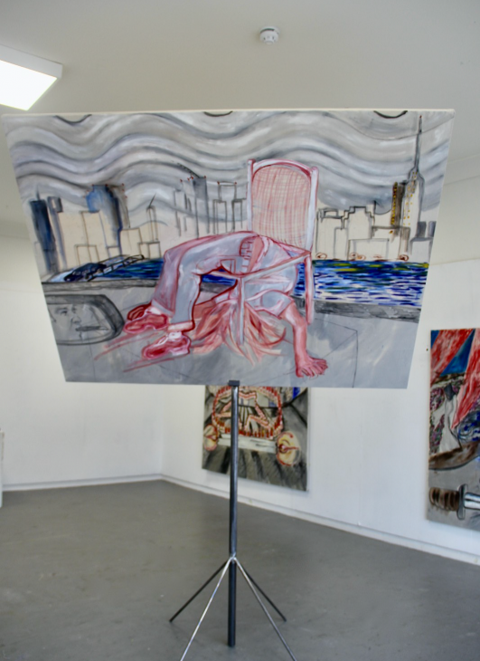 Painting on canvas with a figure in the centre bent over backwards through the seat of a chair in front of a cityscape. Canvas tilted forward on a metal display stand