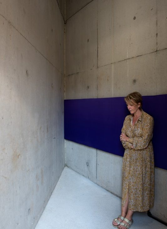 Woman in dress and sandals leaning against a wall based cushioned blue ribbon listening to sound installation
