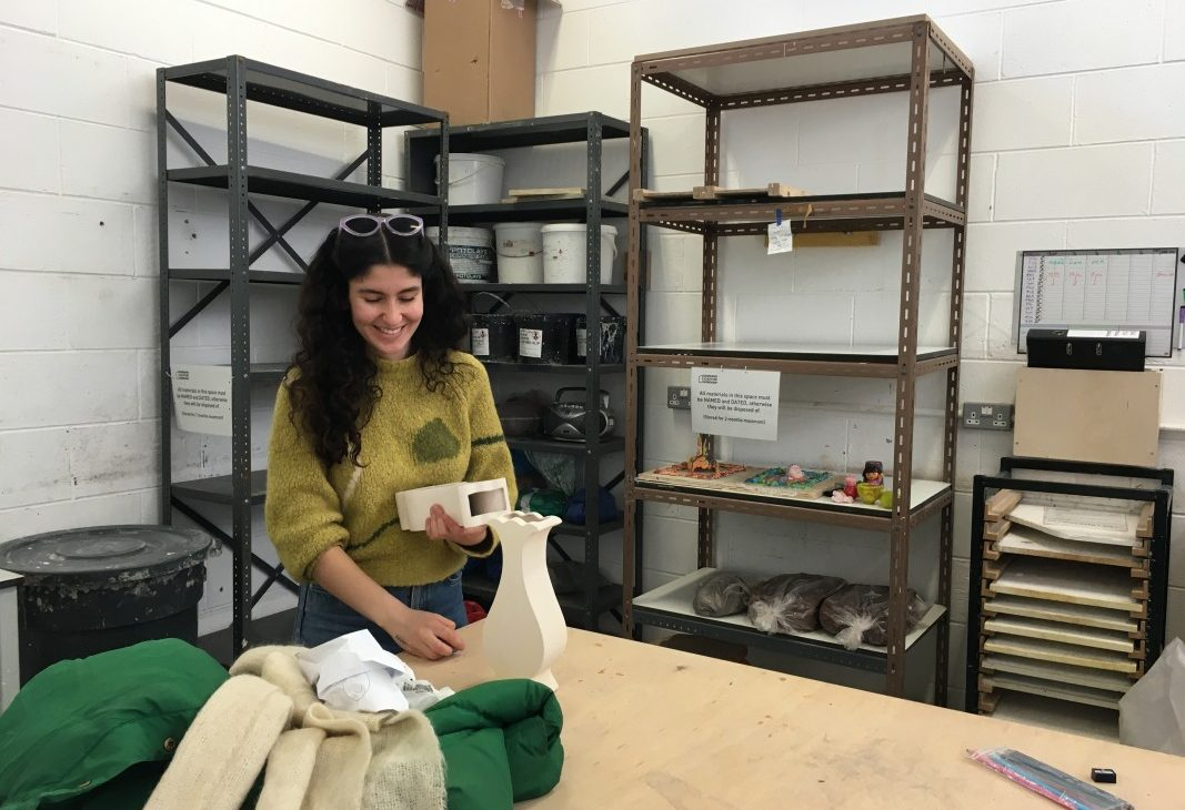 Artist Mina Heydari-Waite in foreground holding two recently fired artworks, white stoneware vases made from slip cast moulds