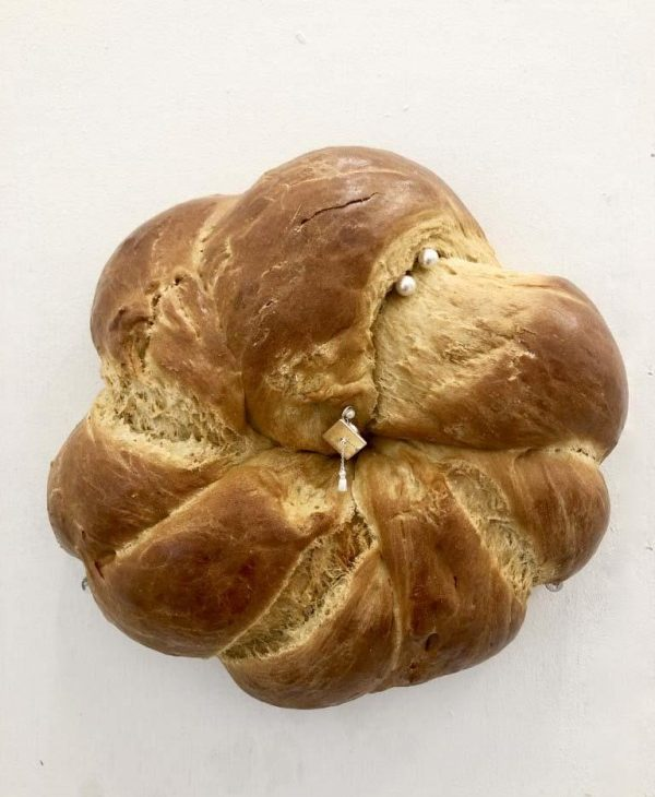Bread bun with interlocking folds, akin to braiding, two pearls on the uppermost fold with a sterling silver square and pearls at the centre of the bun